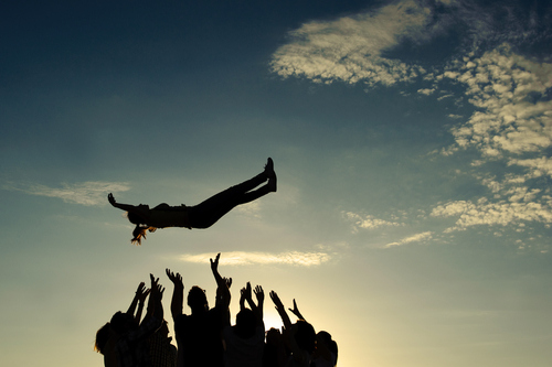 A group of adults throws a child into the blue sky. This represents the team effort required for fostering where support for foster carers is key.